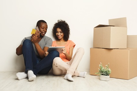 Happy african-american couple discussing design of new appartment, choosing color scheme on tablet, making order on mobile, sitting on floor at white wall near moving and storage boxes, copy space Stock Photo