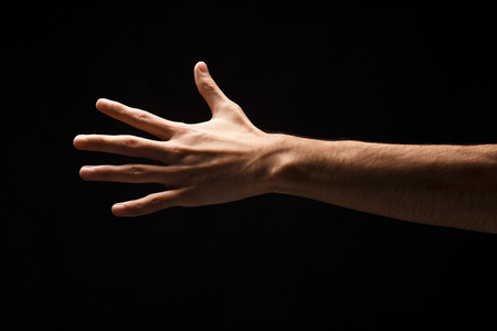 Male hand showing back side of open palm, number five isolated at black background. Counting, gesturing, enumeration concept, cutout, copy space