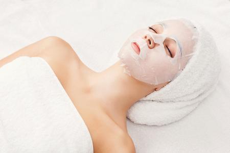 Face mask, spa beauty treatment. Woman applying facial clay mask at spa salon, skincare, top view, overhead Banco de Imagens