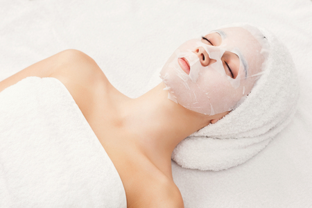 Face mask, spa beauty treatment. Woman applying facial clay mask at spa salon, skincare, top view, overhead Archivio Fotografico