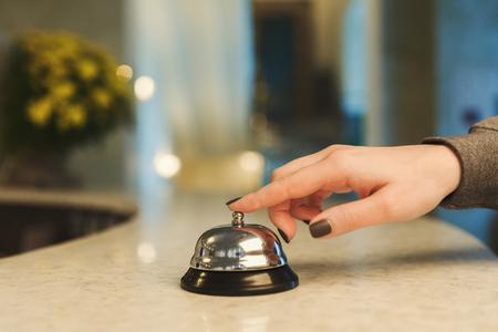 近代的なホテルで注目を集めるためにホテルのサービスベルを鳴らす女性、ぼやけた背景、コピースペース 写真素材