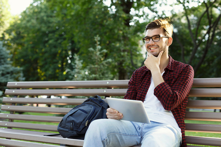 Smiling young man with tablet outdoors. Casual student with backpack checking email and surfing web on digital device, sitting in park. Technology, social media, education and freelance concept.