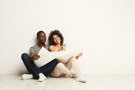 Happy african-american family couple discussing interior design of new appartment, sitting on floor against white wall, copy space, isolated