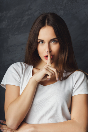 Secret girl. Woman saying be quiet with finger on lips gesture. Privacy concept