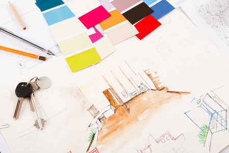 Designers working tools, color swatch and keys on hand painted colored sketch of room interior, closeup