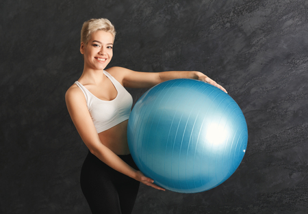 Happy smiling fitness woman training with fitness ball at gym. Young slim girl making aerobics exercise. Healthy lifestyle, gymnastics concept