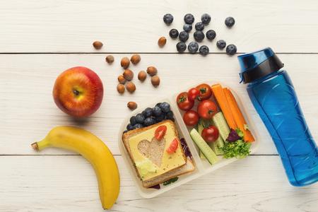 Boîtes à lunch scolaires pour enfant. Vue de dessus sur des collations, des fruits et des légumes sains pour le dîner hors de la maison. Bien manger et concept de stockage des aliments, plat poser, espace copie sur un fond en bois blanc Banque d'images