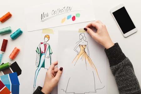 Top view on fashion designer at work. Female hands working with clothes sketch at her creative workspace and using smartphone with empty screen for copy space, top view Foto de archivo