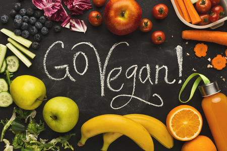 Eating right, vegetarian, motivation and dieting conceptual background. Assortment of organic meals on black chalk board with go vegan inscription and copy space, top view
