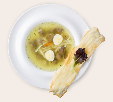 Plate of soup isolated on white background. Diet dish with meatballs, homemade noodles, quail eggs and crusty flat bread, top view, cutout for menu