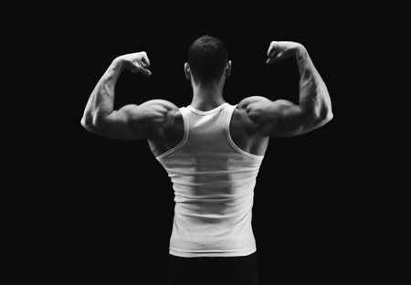 Athletic fitness model shows strong hands and back muscles. Low key, studio shot on black background. Bodybuilding concept, black and white image Stock Photo