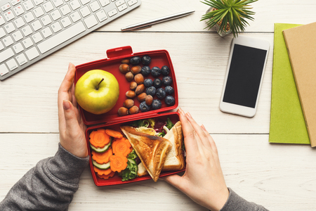 Healthy snack at office workplace. Businesswoman eating organic vegan meals from take away lunch box at wooden working table with computer keyboard and smartphone with empty screen for copy space