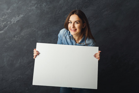 Happy young woman holding white blank banner. Excited girl showing paper sheet for sales advertisement, copy space. Commercial ad mockup