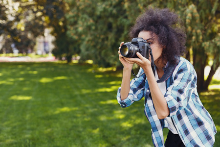 Attractive young happy african-american woman photographing with professional camera outdoors, copy space. Taking photos and photography classes concept