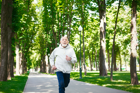 Elderly sporty man running in green park during morning workout, copy space. Healthy and active lifestyle at any age concept