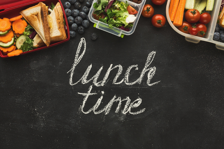 Eating right, storage and dieting conceptual background. Assortment of healthy food in plastic containers on black chalk board with lunch time inscription and copy space, top view