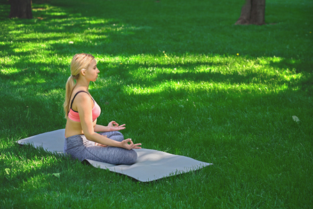 Young woman outdoors, meditation exercises. Girl does lotus pose for relaxation. Wellness, calmness, relax, healthy, active lifestyle concept Zdjęcie Seryjne