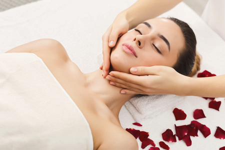 Woman enjoying anti aging facial massage. Pretty girl getting professional skin care at wellness center. Relaxation, beauty, spa and face treatment concept, copy space Stock Photo
