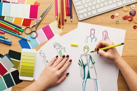 Top view on fashion designer at work. Female hands drawing clothes sketch at her creative workspace and using smartphone with yellow gradient color swatches on screen, top view