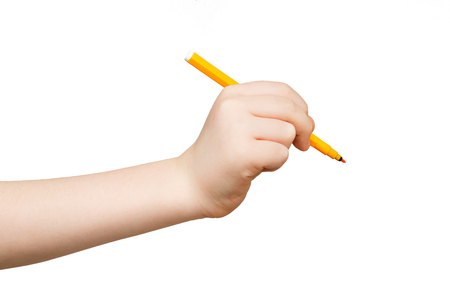 Kid hand holding felt-tip pen, writing or drawing, isolated on white background. Education, art concept Stock Photo