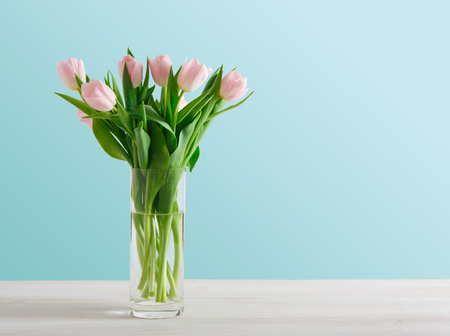 Tender pale pink tulips on blue background, copy space. Bouquet of flowers in glass jar, mockup for mothers day, valentine or wedding greeting card