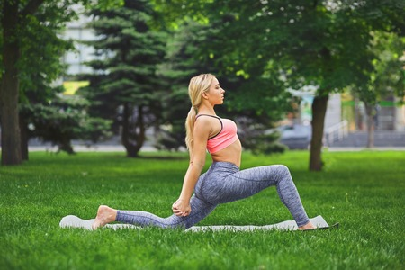 Woman making asana exercises outdoors, in the park. Girl do warrior pose. Stretching, wellness, calmness, relax, healthy, active lifestyle concept Stock Photo