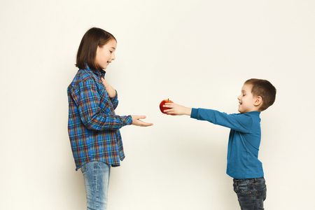 Cute little boy giving his sister an apple, white studio background. Brother treating sis with mall vitamin gift, copy space.