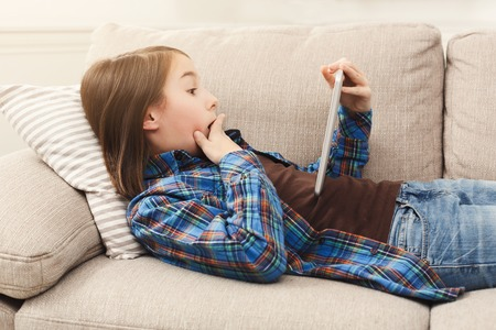 Surprised little girl using digital tablet, lying on beige couch at home, copy space. Shocking news, lottery winning, sale concept