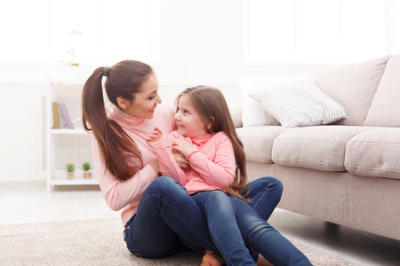 Mother with cute little daughter having fun on the floor in the bedroom. Mothers Day, relationship, motherhood, joint activities and interests, trust, support, caress, maternal warmth, caring concept