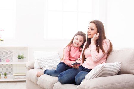 Little girl and her mom listening to music on smartphone at home. Mothers Day, relationship, motherhood, joint activities and interests, trust, support, caress, maternal warmth, caring concept