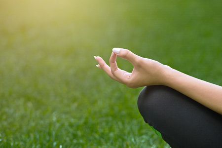 Closeup of yoga woman hand in lotus pose. Girl practicing yoga outdoors. Wellness, calmness, relax, healthy, active lifestyle concept Stock Photo