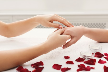 Hand massage at beauty salon. Manicure, nail and skin care at spa on white towel Stock Photo