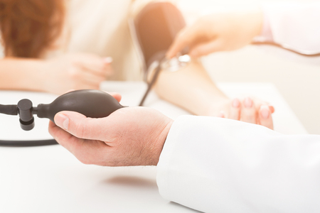 Closeup of doctor hand using tonometer for pulse measurement. Woman stretching her arm. Healthcare and medical, high blood pressure and cardiology concept, copy space