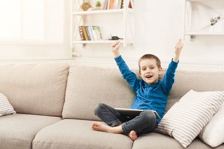 Little boy watching football from digital tablet. Gadgets and technology concept, playing online game while sitting on couch in living room at home, copy space