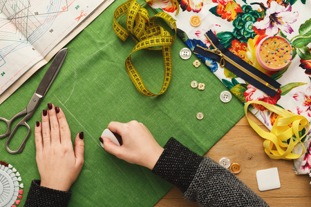 Sewing workshop or fashion designer at work. Top view on female hands marking cloth square with soap piece. Messy table with dressmaker accessories and patterns, copy space Stockfoto