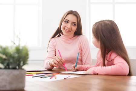 Mother drawing with her daughter. Relationship, motherhood, joint activities and interests, trust, support, caress, maternal warmth, caring, education and early development concept