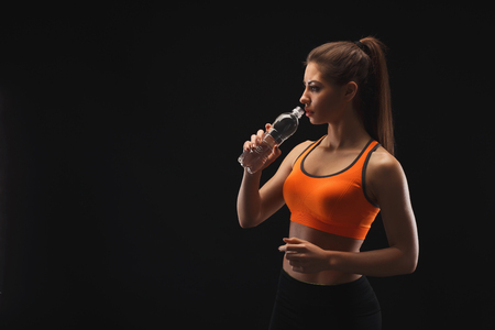 Athletic young woman having rest after bobybuilding training, drinking water on a black background. Studio shot, low key, copy space