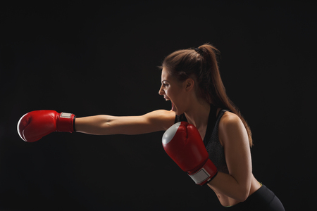 Side view of emotional young woman with boxing gloves and standing in position, ready to fight, copy space. Studio shot on black background, low key. Kickboxing and fight sport concept