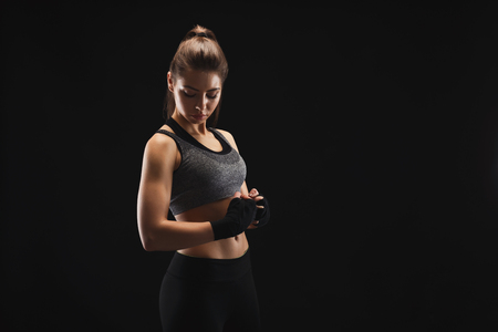 Gorgeous young woman with boxing bandage, ready to fight. Mockup, copy space. Studio shot on black background, low key. Kickboxing and fight sport concept