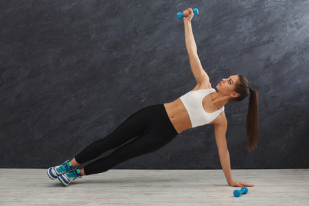 Fitness woman training side plank with dumbbell at grey background indoors. Young slim girl making exercise, copy space