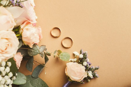 Wedding bride bouquet, floral corsage and two gold rings on beige background with copy space, top view. Preparation, wedding, advertisement, romance concept