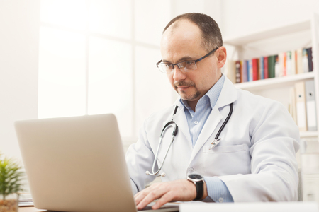 Serious doctor in glasses sitting at the desktop, typing on laptop. Physician is working in bright office, preparing to receive the patient, medicine concept, copy space Stock Photo