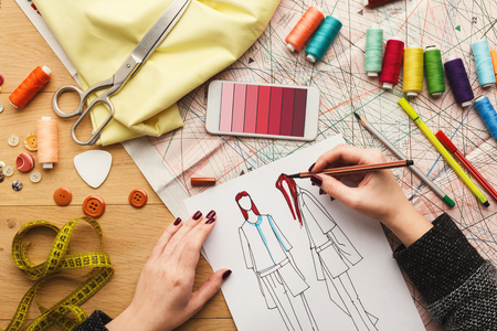Top view on fashion designer at work. Female hands drawing clothes sketch at her creative workspace and using smartphone with color swatches on screen, top view Stock Photo