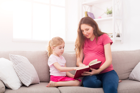 Little girl and her mom reading book sitting on the sofa at home. Mother and daughter study fairy tales. Motherhood, joint activities and interests, early development, caring concept, copy space Stock fotó - 95551633