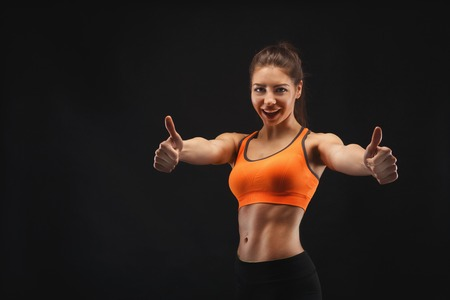 Athletic woman posing in studio and showing thumb up. Muscular body and strong muscles. Shot on black background, low key. Bodybuilding concept Stock Photo