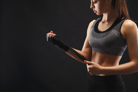 Athletic boxer wrapping hands with boxing tape before fight. Female fitness model with naked torso and muscular body at black studio background, low key. Bodybuilding concept, copy space Stock Photo