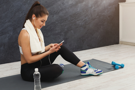 Happy fitness woman having rest and listening to music. Young girl sitting on mat in headphones. Bodybuilding, healthy lifestyle concept, copy space Stock Photo