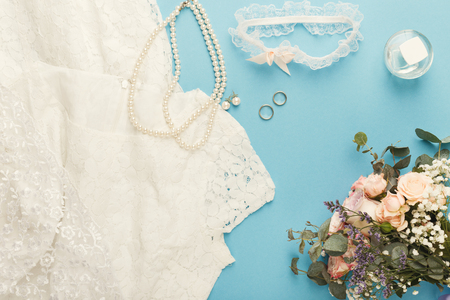 Wedding white dress, accessories, two gold rings, bride bouquet on blue background, closeup, top view. Preparation, wedding, advertisement, romantic background concept
