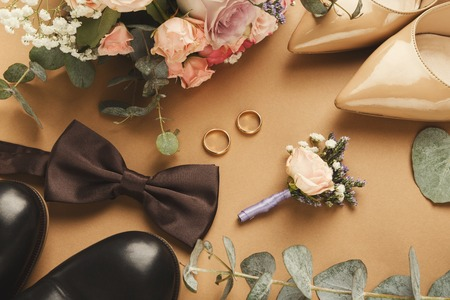 Top view of bride and groom shoes, floral corsage, brown bow-tie, bouquet, golden rings. Preparation for wedding concept, copy space