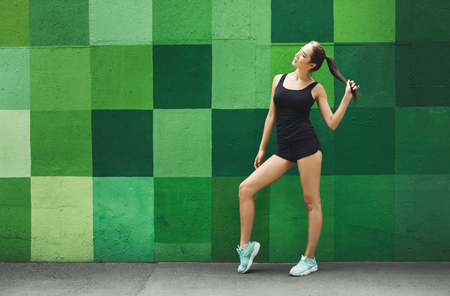 Beautiful fitness girl posing on green wall background outdoors, copy space. Sporty woman with perfect body, healthy lifestyle and bodycare concept Stock Photo